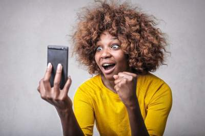 A surprised woman watching a video on her smartphone